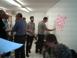 Brainstorming in action. A participant adds to the wall of post it notes at the OKFN workshop.