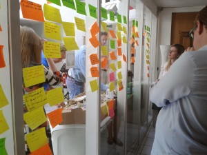 Participants at the OKFN workshop looking at some of the brainstorm post-it notes